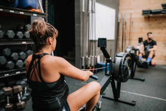 Back view of unrecognizable pregnant female athlete training on rowing machine in modern gym