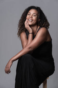 Cheerful young plus size African American female model with long curly hair wearing elegant black dress sitting on chair and looking at camera against gray background