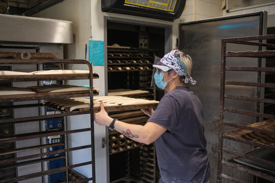 Side view of female in mask and shield putting baking pan with raw baguettes in hot oven while working in bakehouse