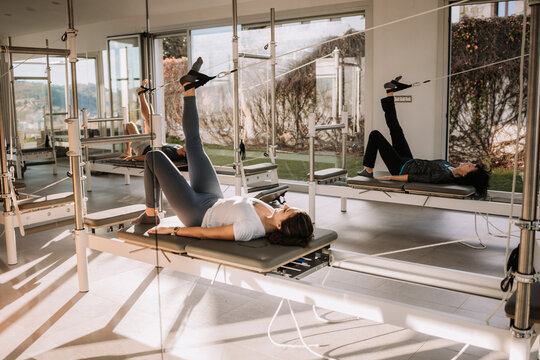 Side view of company of people in activewear lying on pilates reformer with straps in Bridge pose with raised leg and doing yoga in gym together while stretching  body
