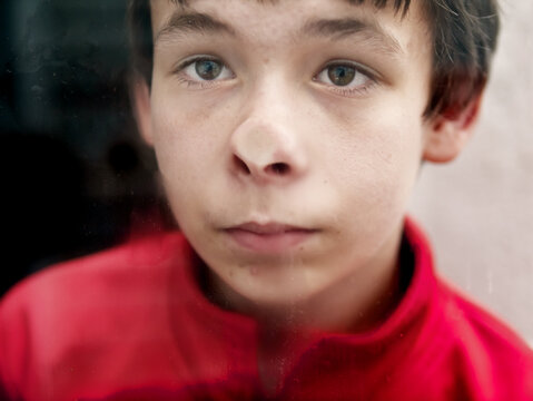 Teenage presses his nose against a window pane