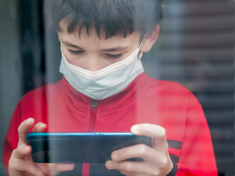 Teenage boy with medical mask at home behind a window using his smart phone to be connected