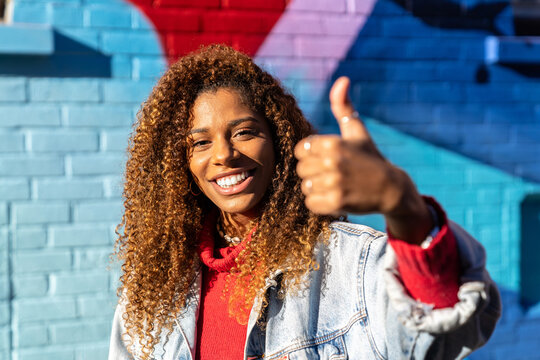 Optimistic young black female millennial with curly hair in stylish clothes showing thumbs up gesture and smiling while looking at camera against blue wall