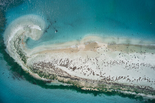 Picturesque drone view of small uninhabited island with sandy coastline and lakes surrounded by turquoise sea water in sunny weather