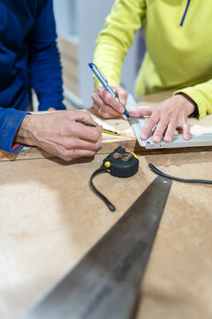From above of crop anonymous man and woman drawing line while measuring wooden plank with ruler during carpentry process in workshop