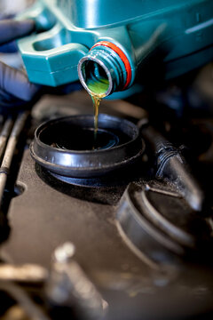 Serious male mechanic pouring engine oil in motor of car while working in repair service
