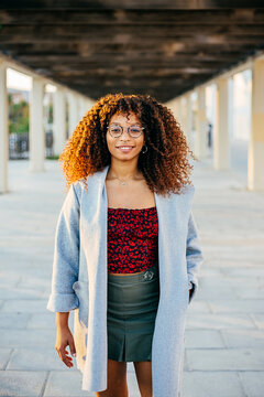 Young black female in trendy outfit and glasses looking at camera while standing under roof on city street