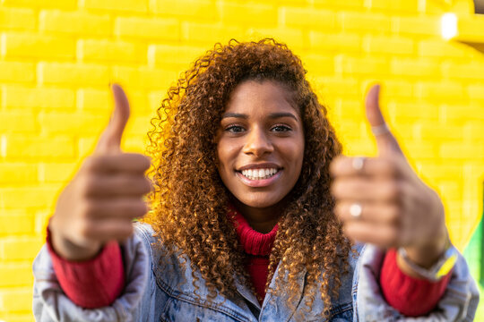 Optimistic young black female millennial with curly hair in stylish clothes showing thumbs up gesture and smiling while looking at camera against yellow wall