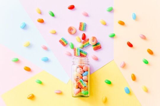 Mixed colorful candies scattered from glass bottle on colorful background. Top view