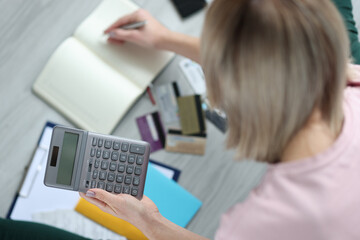 Woman holding calculator in hands and writing in notebook closeup