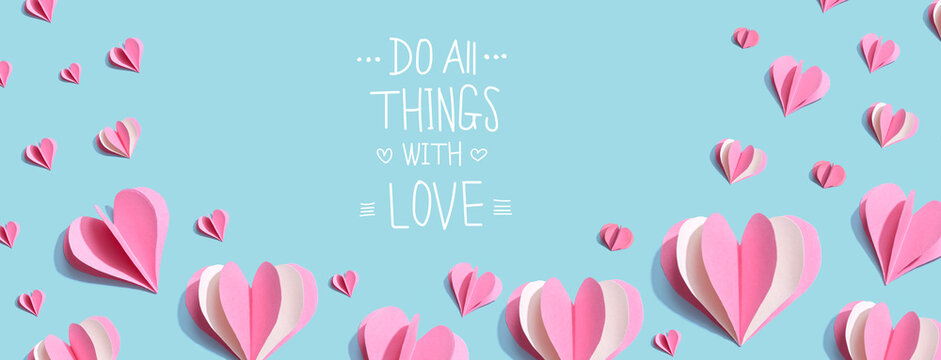 Do all things with love message with pink paper hearts - flat lay