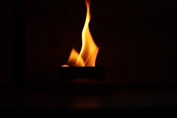 wielki  płomień   palącej  się  świecy  w  ciemnym  pokoju