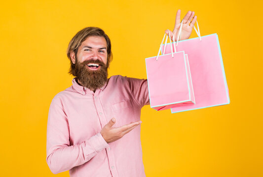 Heavy bags. commonly used for birthday. buy anniversary gifts. surprised male open shopping bag with something exciting inside. mature man looking casual in surprise with present package