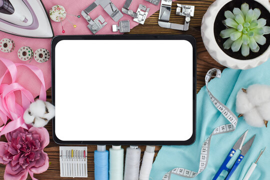 Online sewing courses. Sewing background. Various items for the seamstress. A tablet with a copy of the space around it sewing equipment. Flat lay. Top view.