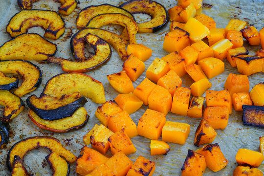 Roasted butternut squash cubes and acorn squash slices on parchment paper on a baking sheet