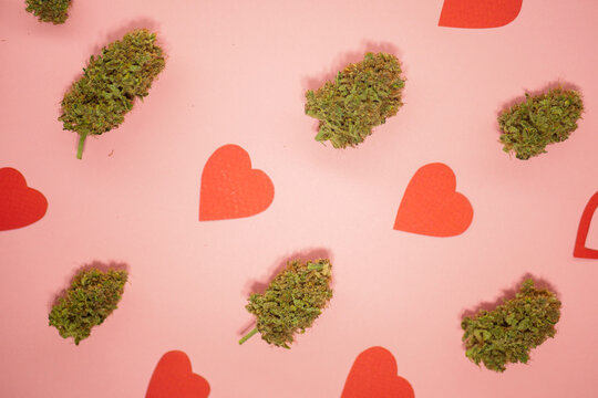 Cannabis buds pattern. Valentines day wallpaper. Red paper hearts