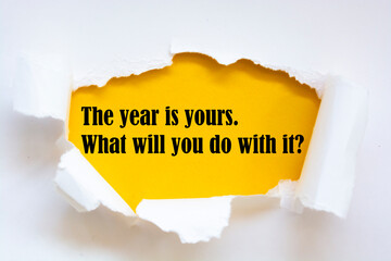 Motivational quote The year is yours. What will you do with it? appearing behind torn white paper.