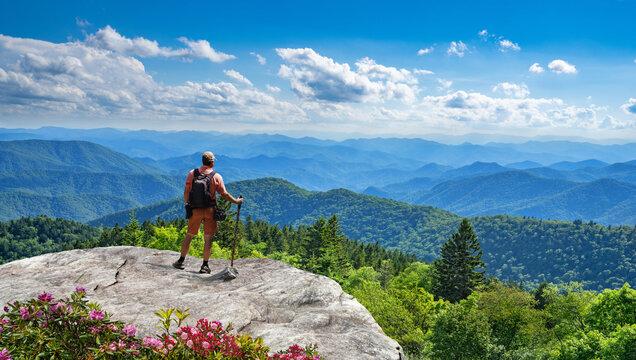 Man standing on top of the mountain relaxing and  enjoying beautiful summer mountain landscape. Near Asheville, Blue Ridge Mountains, North carolina, USA.