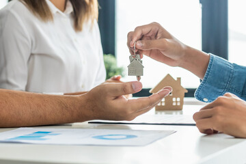 Fototapeta Close up hand of home,apartment agent or realtor was holding the key to the new landlord,tenant or rental.After the banker has approved and signed the purchase agreement successfully.Property concept.
