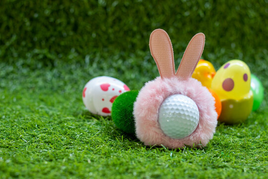 Golf Easter with rabbit hat on golf ball with Easter eggs behind on green grass