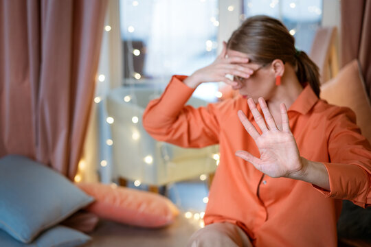 Woman on background window covers her face with her hand and shows stop gesture