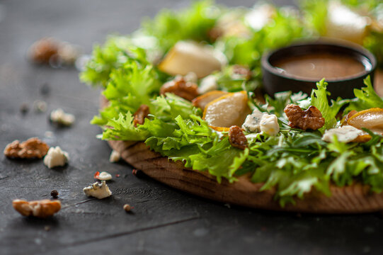 Light diet salad with pear, nuts and blue cheese. The salad is laid in the form of a wreath on a round wooden board with sauce in the center on a dark background.