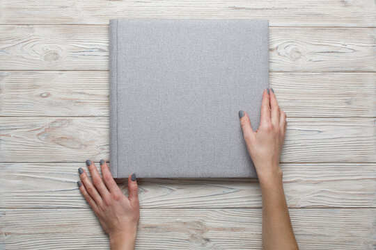 person touch and open a photobook. Family photoalbum on the table. womans hand holding a grey family photo album with copy space for text. stylish wedding photo album on light background