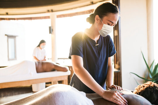 Spa massage therapist with face mask working in the new normal