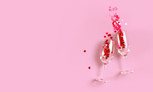 Two clinking champagne glasses with splash of red heart shaped confetti over pink background. Overhead view, copy space. 3D rendering illustration.