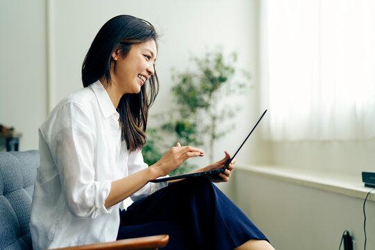 ノートパソコンを見る30代日本人女性