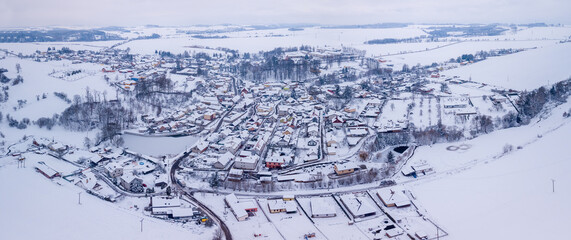 Aerial view of village Puklice with residential buildings in winter. Winter landscape snow covered field and trees in countryside. Czech Republic Highland Fotobehang