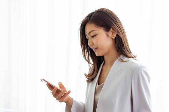スマートフォンを見る30代ビジネスウーマン
