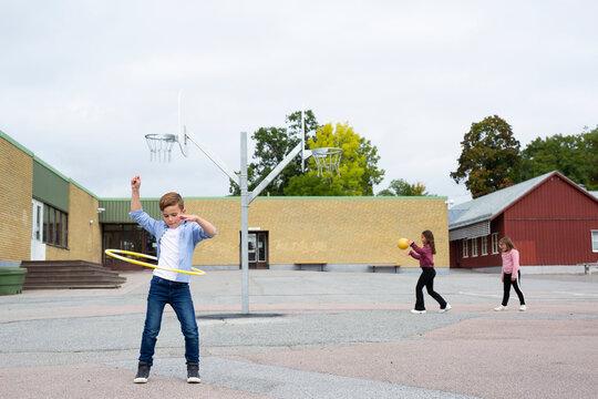 Boy spinning plastic hoop on school yard