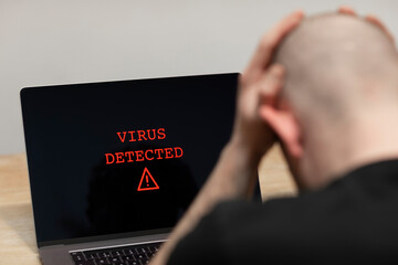 Virus detected with a warning sign on a laptop. A desperate man sitting in front of his computer with the warning on his screen. Cybercrime, infected unsafe device - fototapety na wymiar