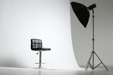 Modern chair and professional lighting equipment in photo studio