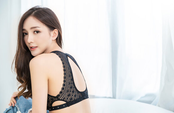 Portrait of asian woman in black lace top bra lingerie underwear boudoir. Beauty asian girl with bare skin shoulder back in her morning routine. Sexy girl in bedroom modern asia lifestyle concept