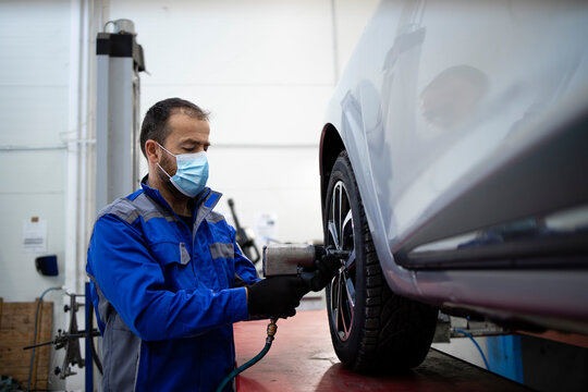Professional car mechanic wearing face mask due to corona virus holding pneumatic screw gun and changing wheels of vehicle. Automobile service and maintenance.