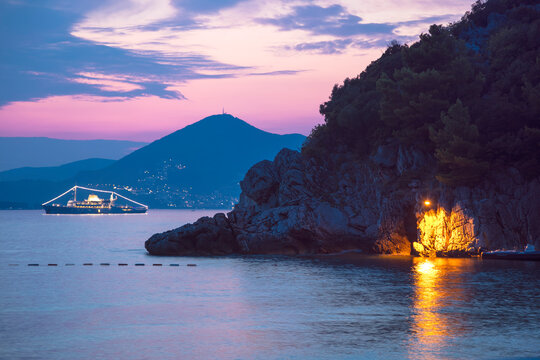 Stunning Montenegro Sunsets From Waterfront Restaurants  Hotel Balconies And Seaside Cliffs.  The photo is taken in the city of Sveti Stefan  at sunset. In the distance we see a cruise ship.