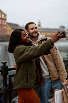 Young couple taking selfie near canal in town