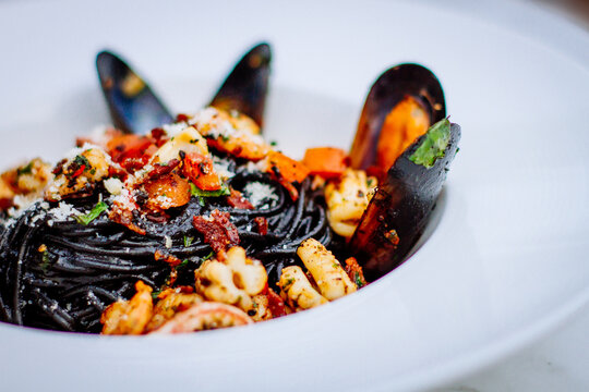 Squid ink pasta with king prawns, herbs and chilli sauce