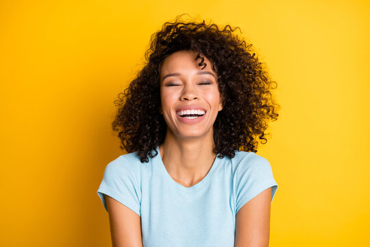 Photo of adorable funny dark skin curly woman dressed blue t-shirt laughing closed eyes isolated yellow color background