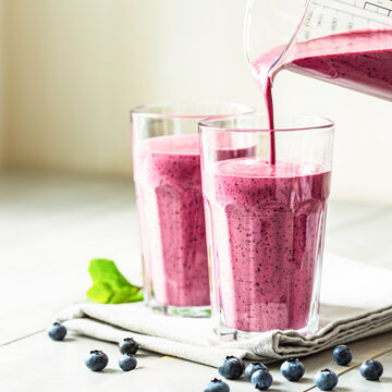 Two glasses of blueberry smoothie with mint garnish and straw on the table. Berry shake is poured into a glass.