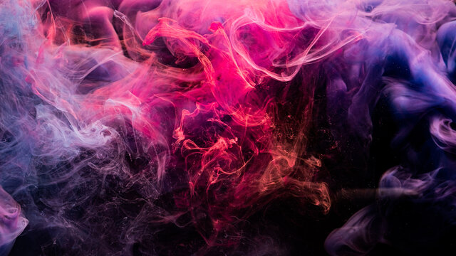 Ink in water. Colorful background. Abstract fume cloud texture. Mystic energy. Glowing bright neon magenta pink purple mist floating on dark.
