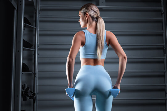 Beautiful tall blonde posing in the gym with dumbbells in her hands against the background of the wall bar. The concept of sports, fitness, aerobics, bodybuilding, stretching. Back view.