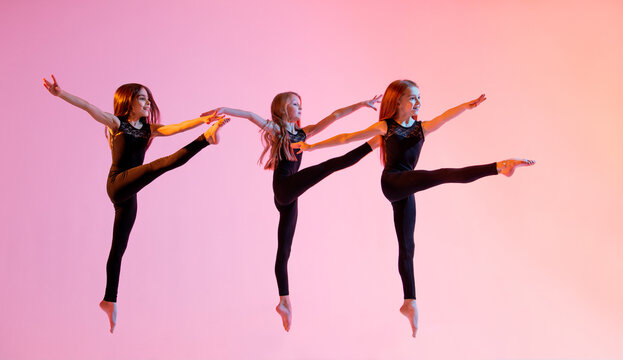 group of three ballet girls in black tight-fitting suits jumping on red background with their long hair down.