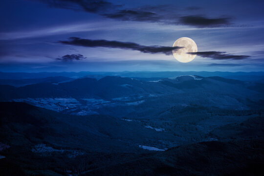 mountain landscape on a summer night. hills rolling from the valley up in to the distant ridge. view of the summer scenery in full moon light