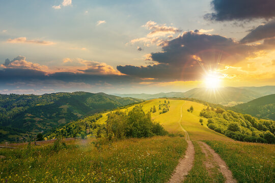 road through meadow in mountains at sunset. beautiful rural landscape of carpathians in evening light. wonderful summer weather with fluffy clouds on the sky