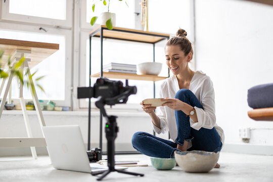 Female vlogger making social media video about her pottery