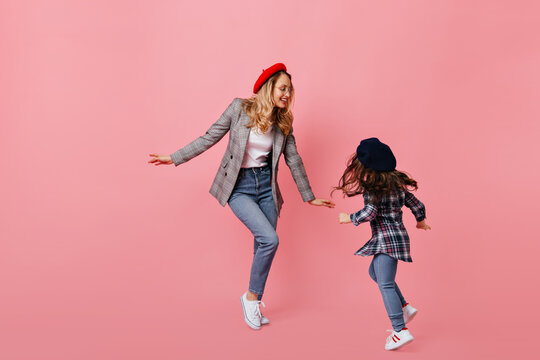 Stylish curly blond woman in jeans and gray jacket dancing with her little dark-haired daughter on pink background
