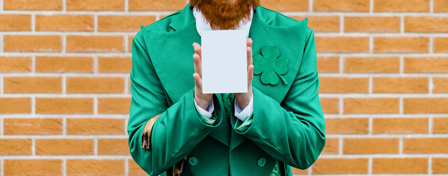 St. Patrick's Day celebration postcard template, layout. man in st patrick costume holding blank postcard against brick wall background